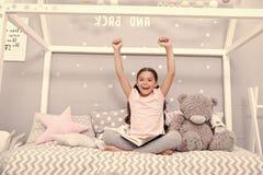 Aprecie o conceito A menina feliz aprecia ficar na cama A crian?a pequena com m?os levantadas aprecia o livro de leitura Aprecie  foto de stock