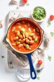 Aprecie seus feijões cozidos com alho e os tomates frescos imagens de stock