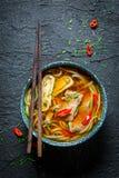 Aprecie sua sopa vermelha do caril com hashis fotografia de stock