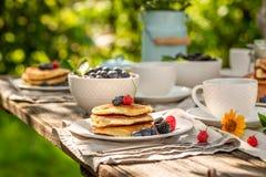 Aprecie suas panquecas servidas com café no jardim imagens de stock