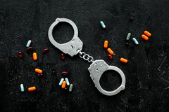 Apreensão para o conceito ilegal das drogas da compra, da possessão e da venda Drogas como comprimidos perto da algema na parte s fotos de stock