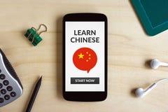 Aprenda el concepto chino en la pantalla elegante del teléfono en el escritorio de madera imágenes de archivo libres de regalías