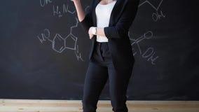 Aprenda el fondo hermoso confiado de la pizarra de la tiza del profesor de la mujer de la fórmula de la ciencia o de la química almacen de metraje de vídeo