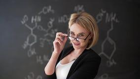 Aprenda el fondo hermoso confiado de la pizarra de la tiza del profesor de la mujer de la fórmula de la ciencia o de la química almacen de video