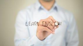 Aprenda el inglés, escritura del hombre en la pantalla transparente Imagenes de archivo