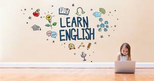 Aprenda el texto inglés con la niña que usa un ordenador portátil imágenes de archivo libres de regalías