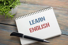 Aprenda el texto inglés escrito en la página del cuaderno, el lápiz rojo y la taza de café Opinión de sobremesa del escritorio de Fotografía de archivo