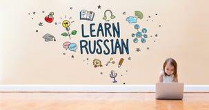 Aprenda el texto ruso con la niña que usa un ordenador portátil fotos de archivo