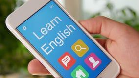 Aprenda el uso inglés del concepto en el smartphone El hombre utiliza el app móvil metrajes
