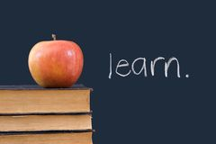Aprenda escrito en la pizarra con la manzana y los libros Imagen de archivo libre de regalías