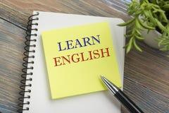 Aprenda o texto inglês escrito na página do caderno, no lápis vermelho e no copo de café Opinião de tampo da mesa da mesa de escr Fotografia de Stock Royalty Free