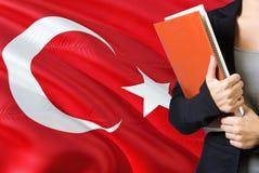 Aprendendo o conceito turco da língua Posição da jovem mulher com a bandeira de Turquia no fundo Professor que guarda livros, lar fotos de stock