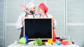 Aprendendo técnicas clássicas para pratos Pares de homem e de mulher que gesticulam está bem na placa em cozinhar a escola Cozinh imagem de stock royalty free