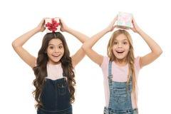 Aprendido como ao papel de embrulho Meninas felizes que guardam caixas de presente em cima Crianças pequenas com blocos do presen fotografia de stock royalty free