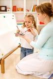 Aprendiendo cómo pintar con la mama Fotos de archivo