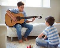 Aprendiendo cómo tocar la guitarra Fotos de archivo
