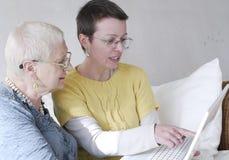 Aprendiendo a una mujer mayor cómo utilizar un ordenador Foto de archivo