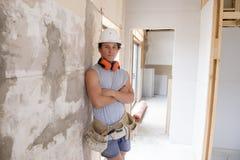 Aprendiz atractivo y confiado joven del trabajo del constructor y del constructor que aprende y que trabaja en el cuello azul del fotografía de archivo