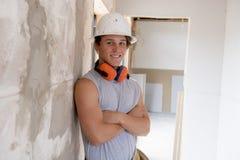 Aprendiz atractivo y confiado joven del trabajo del constructor y del constructor que aprende y que trabaja en el cuello azul del fotos de archivo