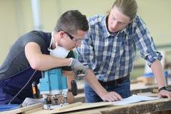 Aprendiz con el monitor caropentry que trabaja en la madera Fotografía de archivo