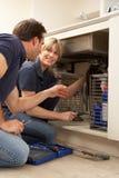 Aprendiz de ensino do canalizador para reparar o dissipador de cozinha Foto de Stock Royalty Free