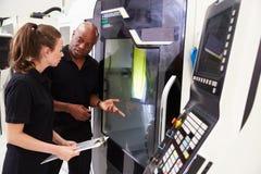 Aprendiz fêmea que trabalha com maquinaria do CNC de On do coordenador imagens de stock