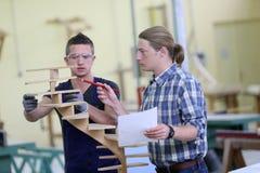 Aprendiz joven con el instructor de la carpintería que trabaja en la madera Imágenes de archivo libres de regalías