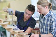 Aprendiz joven con el instructor que trabaja en la madera Fotos de archivo libres de regalías