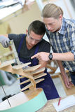 Aprendiz joven con el instructor que trabaja en la madera Foto de archivo libre de regalías