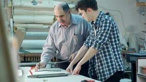 Aprendiz joven que estudia cómo construir un marco, trabajador mayor que habla con él detrás del escritorio en taller del marco metrajes