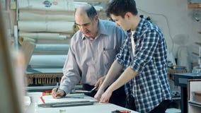Aprendiz joven que estudia cómo construir un marco, trabajador mayor que habla con él detrás del escritorio en taller del marco Imagen de archivo