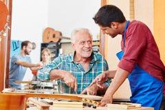 Aprendiz mais luthier mestre das ajudas imagem de stock royalty free