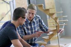 Aprendiz novo com instrutor da carpintaria imagem de stock royalty free