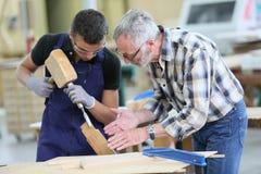 Aprendiz novo na carpintaria com instrutor fotos de stock royalty free