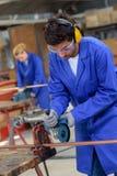 Aprendiz que usa la sierra de la circular en taller de la metalurgia fotos de archivo libres de regalías