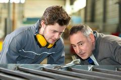Aprendiz y profesor que trabajan con las barras de metal en fábrica Fotos de archivo