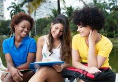 Aprendizagem de riso de três estudantes fêmeas exterior Fotos de Stock
