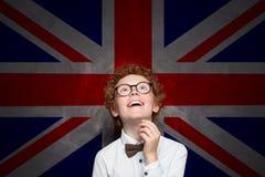 Aprendizagem engraçada da criança inglesa Estudante do rapaz pequeno no fundo BRITÂNICO da bandeira foto de stock