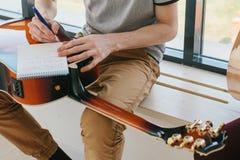Aprendizagem jogar a guitarra Lições da educação e do extracurricular da música foto de stock