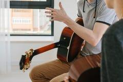 Aprendizagem jogar a guitarra Lições da educação e do extracurricular da música fotografia de stock