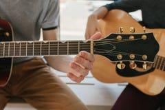 Aprendizagem jogar a guitarra Lições da educação e do extracurricular da música Passatempos e entusiasmo para jogar a guitarra e imagens de stock