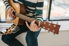 Aprendizagem jogar a guitarra Lições da educação e do extracurricular da música Passatempos e entusiasmo para jogar a guitarra e foto de stock
