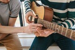 Aprendizagem jogar a guitarra Lições da educação e do extracurricular da música Passatempos e entusiasmo para jogar a guitarra e fotos de stock