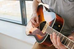 Aprendizagem jogar a guitarra Lições da educação e do extracurricular da música Passatempos e entusiasmo para jogar a guitarra e fotografia de stock royalty free