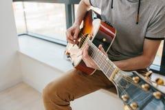 Aprendizagem jogar a guitarra Lições da educação e do extracurricular da música Passatempos e entusiasmo para jogar a guitarra e imagens de stock royalty free