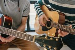 Aprendizagem jogar a guitarra Lições da educação e do extracurricular da música Passatempos e entusiasmo para jogar a guitarra e imagem de stock