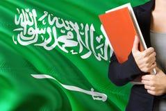 Aprendizaje de concepto árabe de la lengua Situación de la mujer joven con la bandera de la Arabia Saudita en el fondo Profesor q fotos de archivo libres de regalías