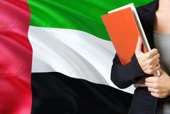 Aprendizaje de concepto de la lengua de Emirian Situación de la mujer joven con la bandera de United Arab Emirates en el fondo Te imagenes de archivo