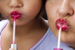 Aprendizaje de enseñanza del lápiz labial de la hija de la madre Imágenes de archivo libres de regalías