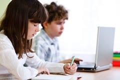 Aprendizaje de la muchacha y del muchacho Imágenes de archivo libres de regalías